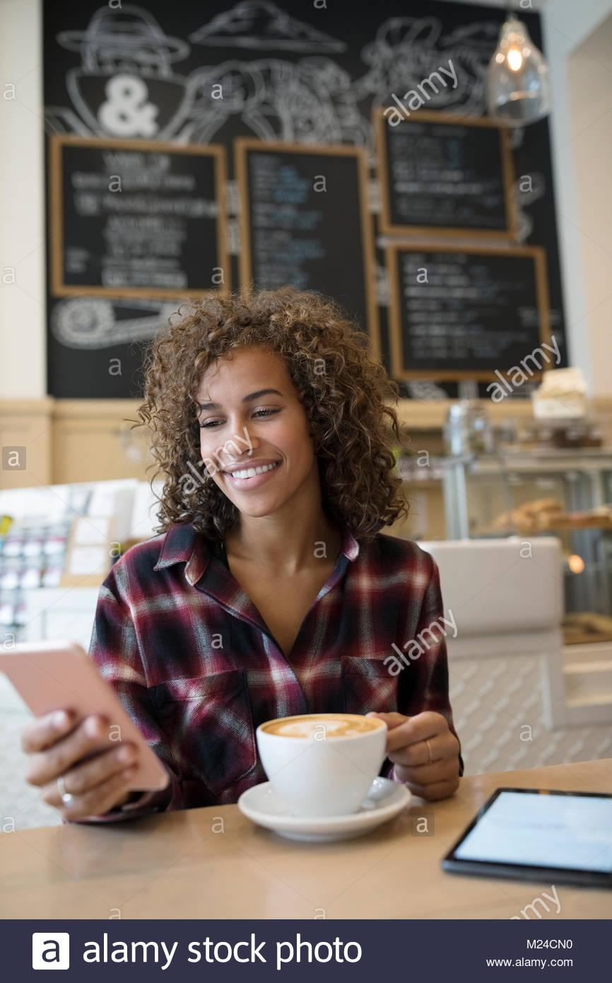 Sorridente giovane donna texting con smart phone e bere cappuccino in cafe Immagini Stock