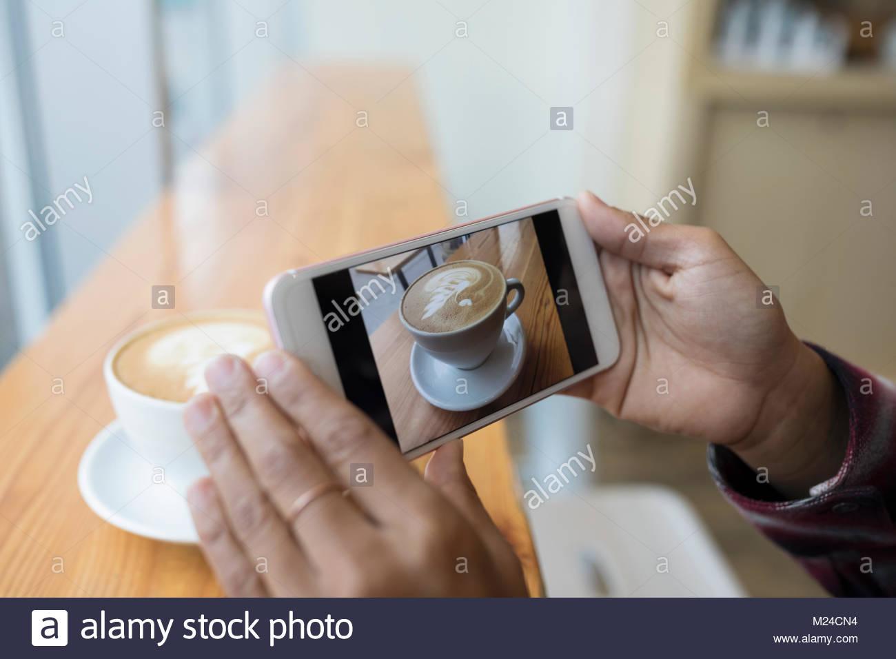 Vicino la donna con la fotocamera del telefono a fotografare il cappuccino in cafe Immagini Stock