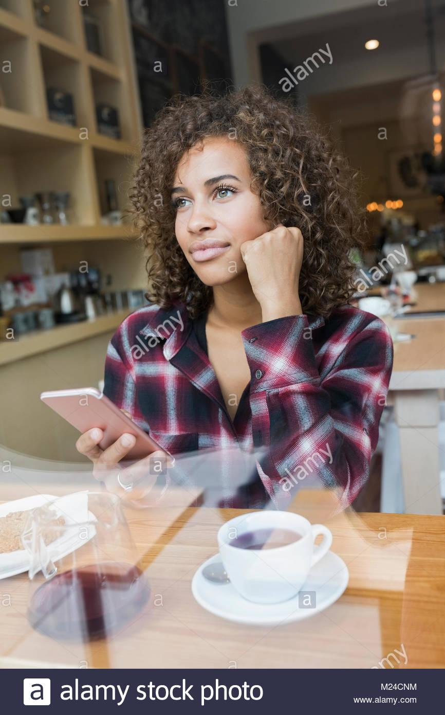 Considerato giovane donna texting con smart phone e di bere il caffè nella caffetteria Foto Stock