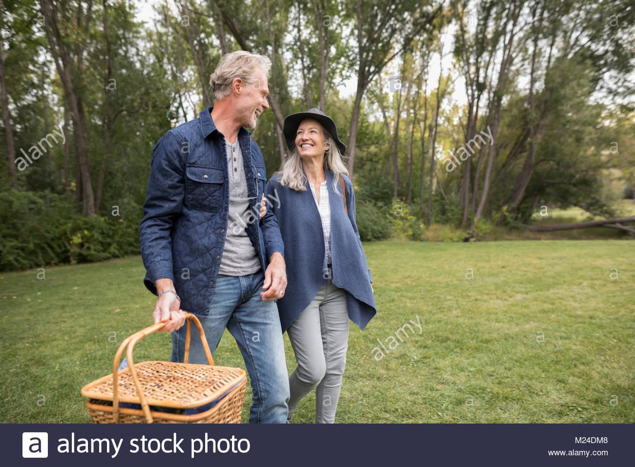 Sorridente coppia senior a piedi, portando un cestino picnic nel parco Immagini Stock