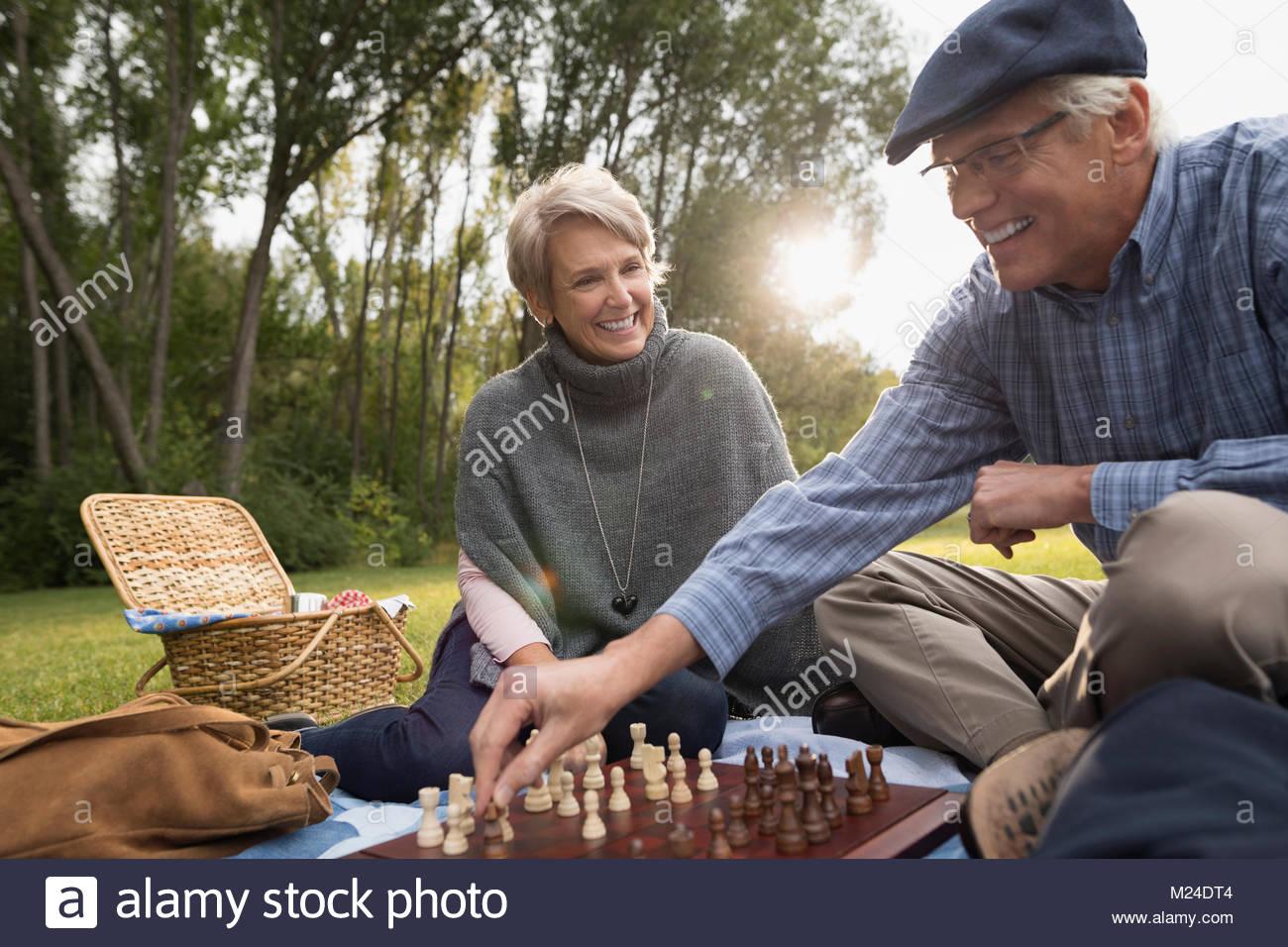 Coppia senior giocando a scacchi in posizione di parcheggio Immagini Stock