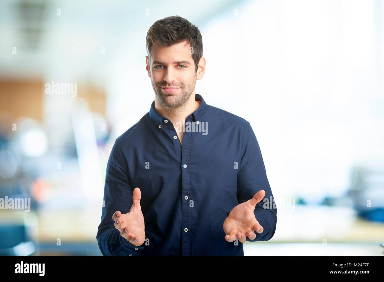 Ritratto di giovane sorridente imprenditore in piedi con le braccia alzate in ufficio. Immagini Stock