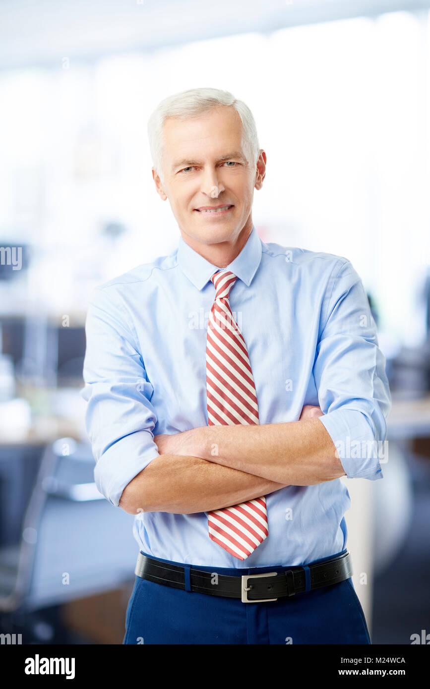 Un dirigente senior advisor finanziario imprenditore in piedi con le braccia incrociate in ufficio e guardando la Immagini Stock
