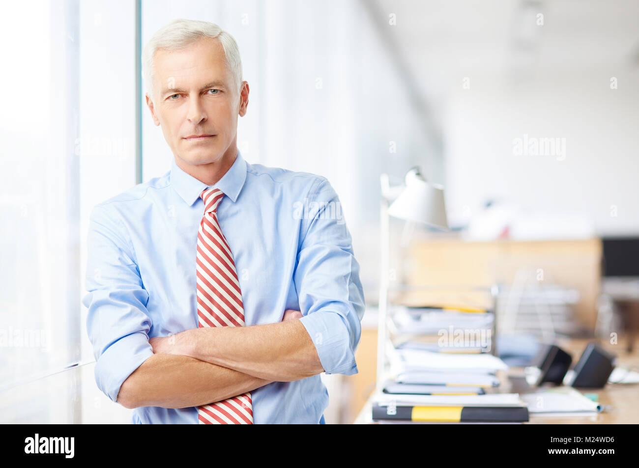 Un dirigente responsabile delle vendite in piedi con le braccia incrociate in ufficio e guardando la fotocamera. Foto Stock