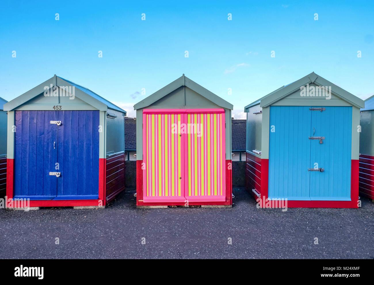 Brighton Seafront tre cabine, due con porte blu e quello al centro ha un multi porta colorati di giallo, rosa, strisce Immagini Stock