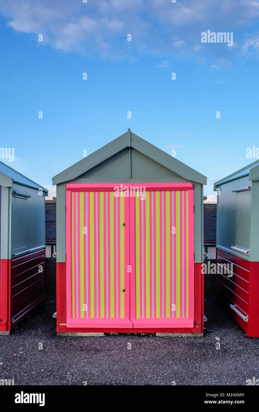 La spiaggia di Brighton capanna con un multi porta colorato di giallo, rosa, strisce nere dietro è il blu del Immagini Stock