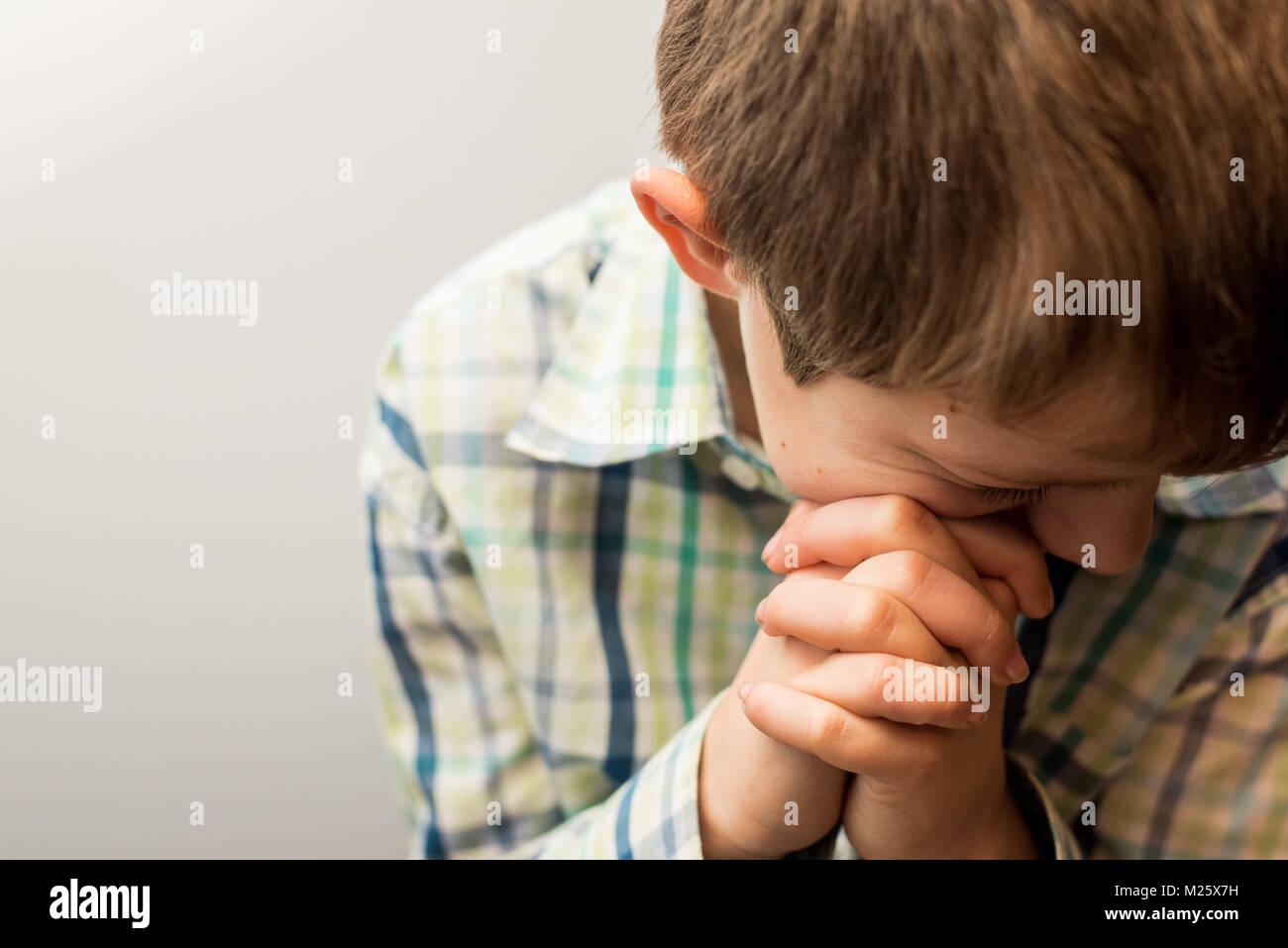 Un giovane ragazzo con la testa piegata nella preghiera Immagini Stock