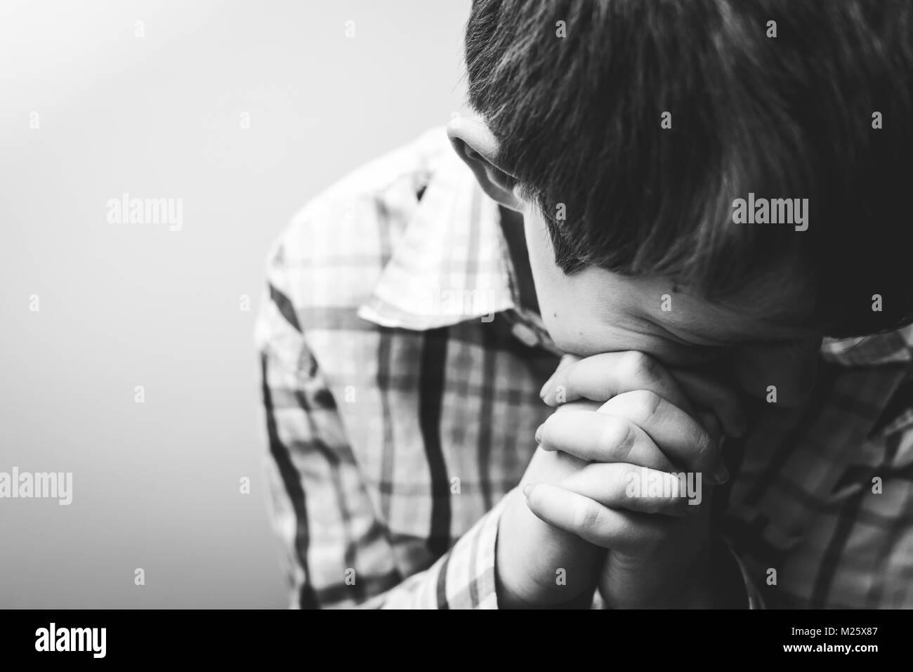 Un giovane ragazzo con la testa piegata nella preghiera. Immagini Stock