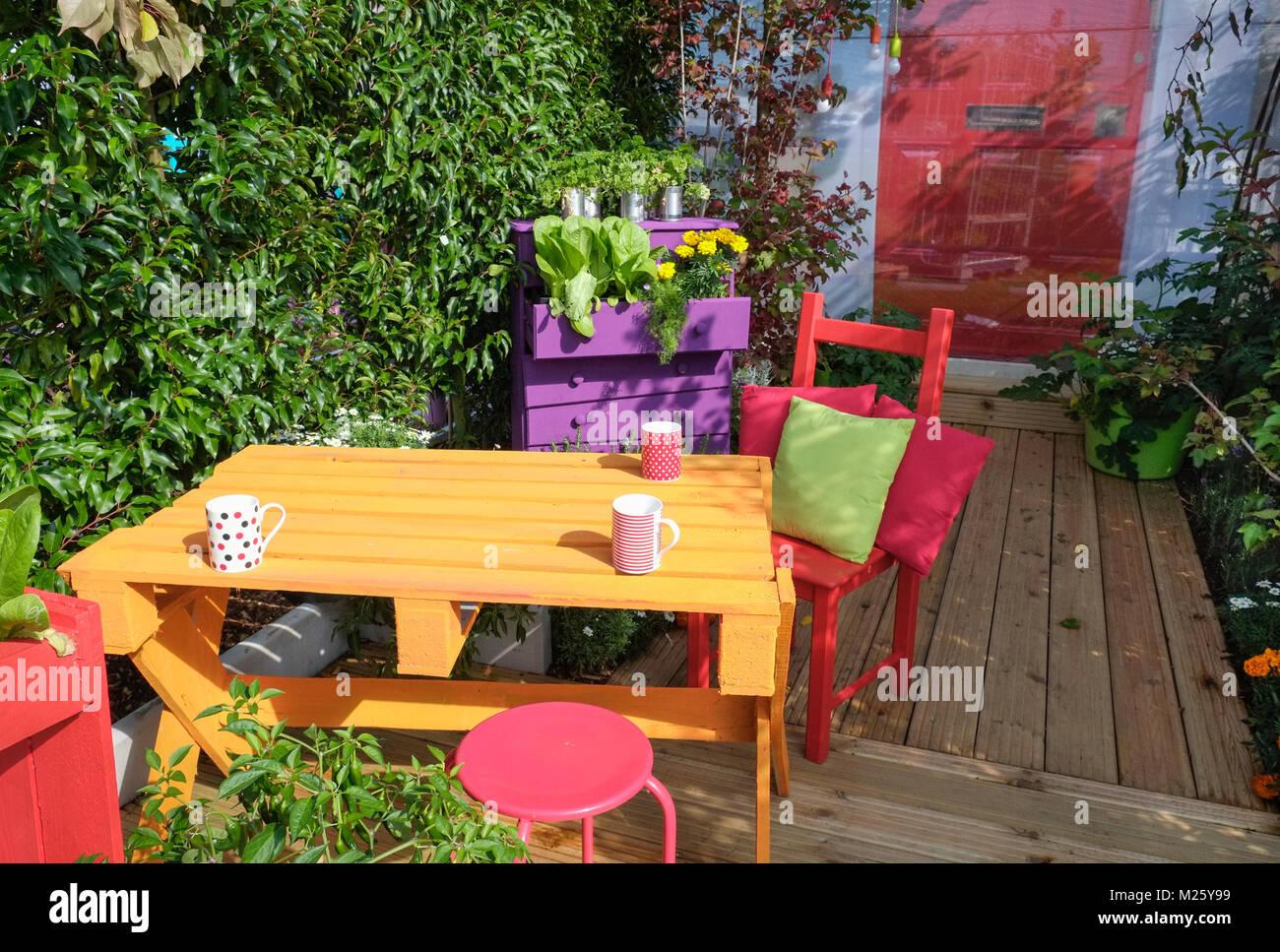 Piccolo giardino esterno area patio con colori luminosi di tavolo
