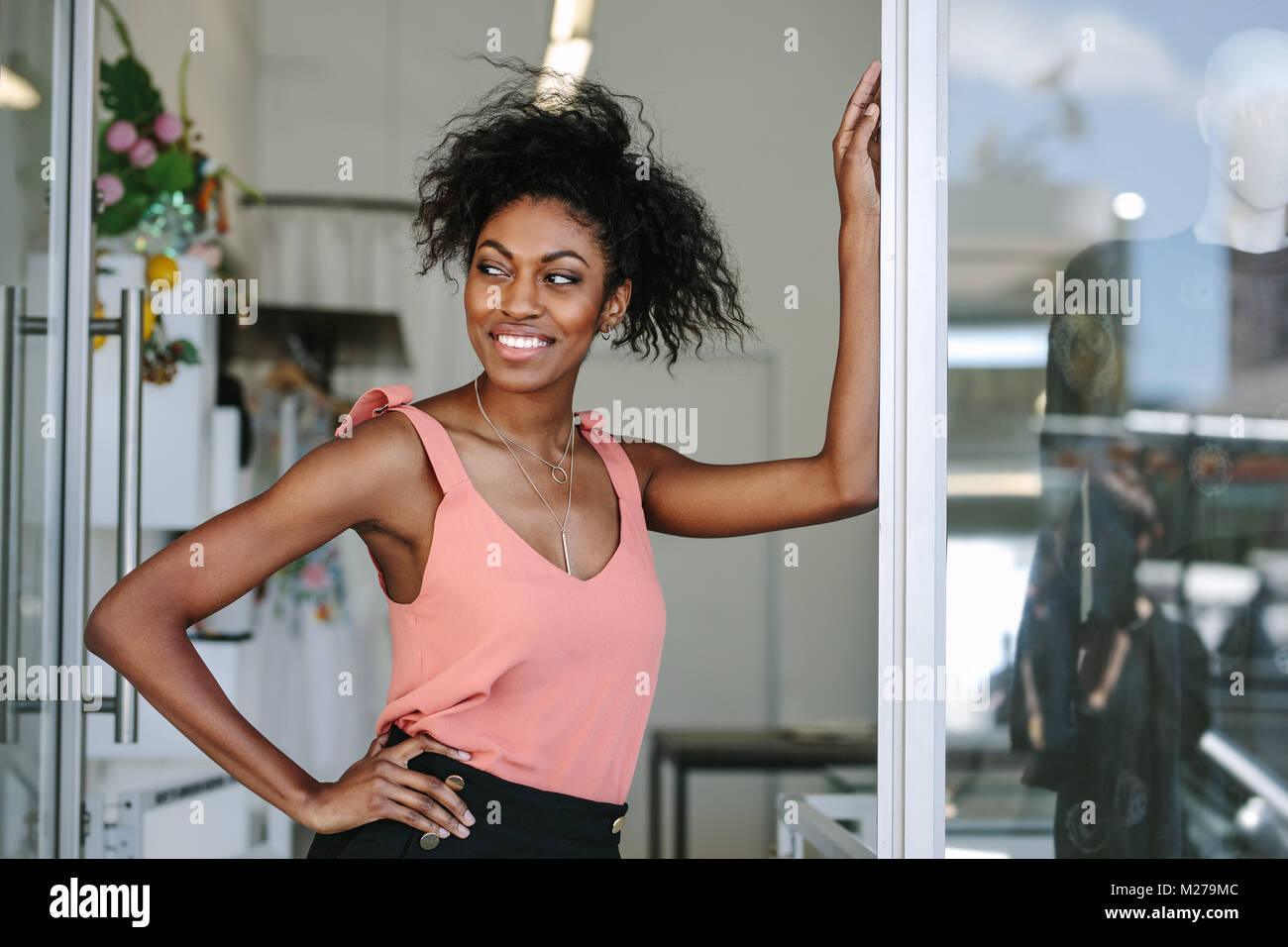 4918e5f64a61 Abito sorridente designer nel suo negozio di stoffa con abiti firmati sul  display. Imprenditrice donna