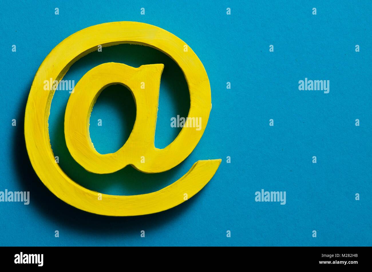 Segno @ per e-mail, giallo su blu Immagini Stock