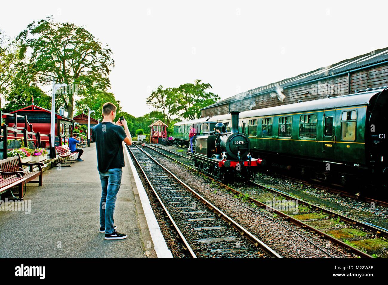 Ragazzo giovane rastrellatura foto con un telefono, Tenterden Town, Kent e East Sussex Railway, Kent Immagini Stock