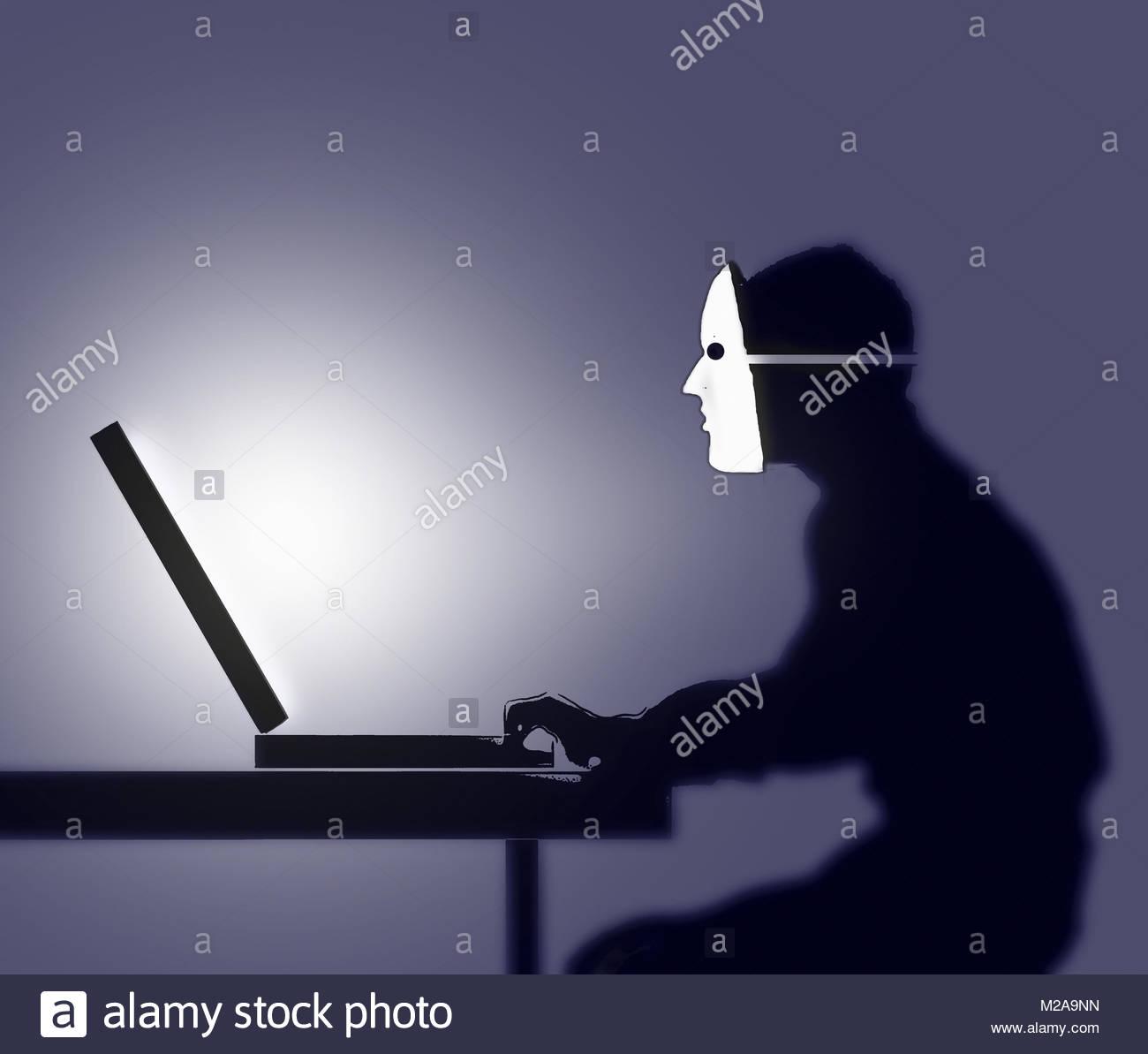 Uomo che indossa maschera utilizzando il computer Foto Stock