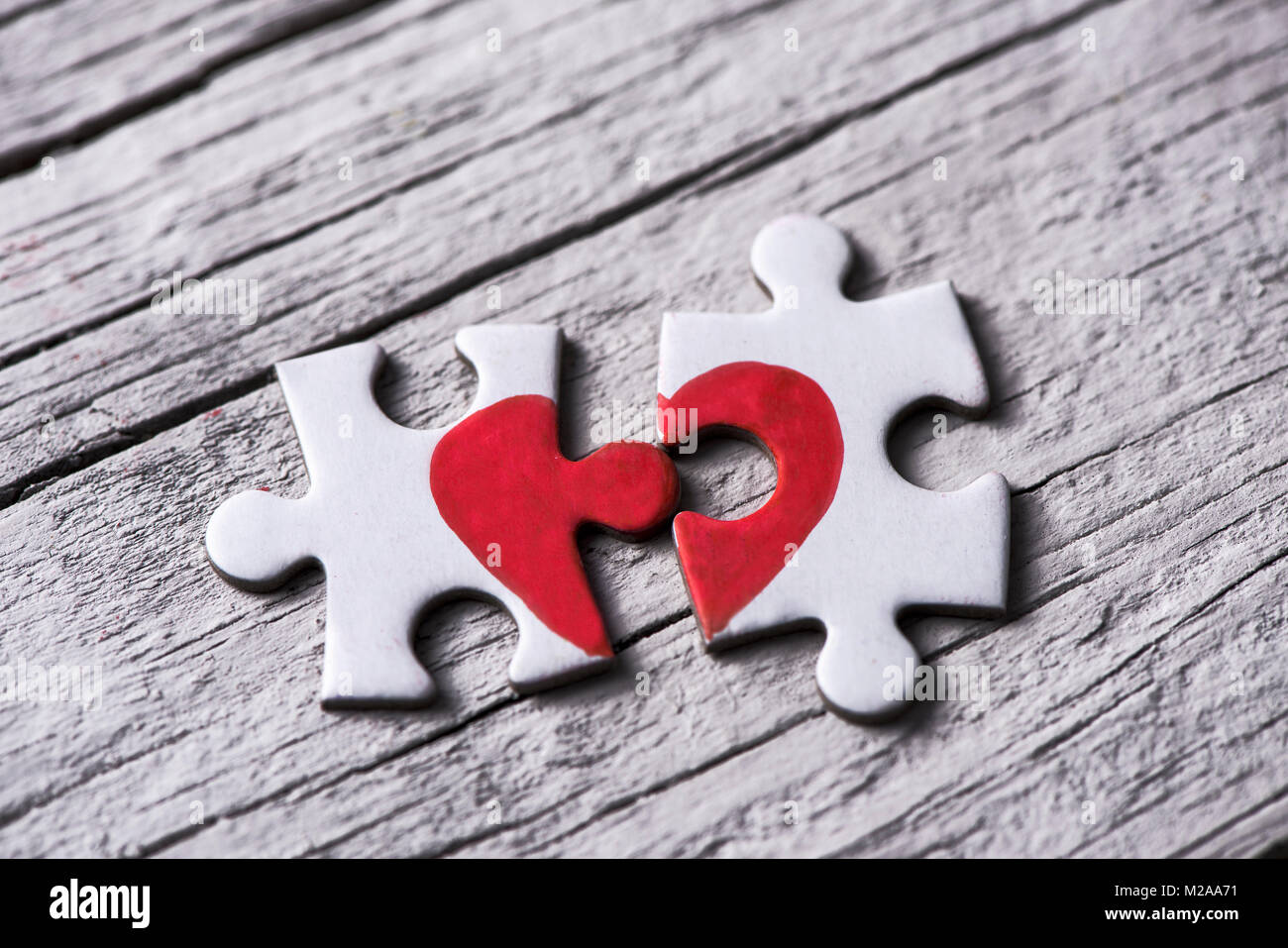 Primo piano di due separate di pezzi di un puzzle che insieme formano un cuore su un bianco rustico superficie in Immagini Stock
