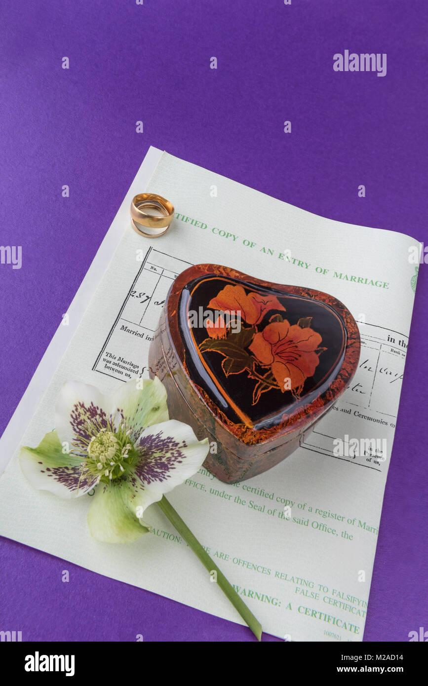A forma di cuore scatola e gli anelli di nozze posati su un certificato di matrimonio.giorno di nozze di amore e Immagini Stock