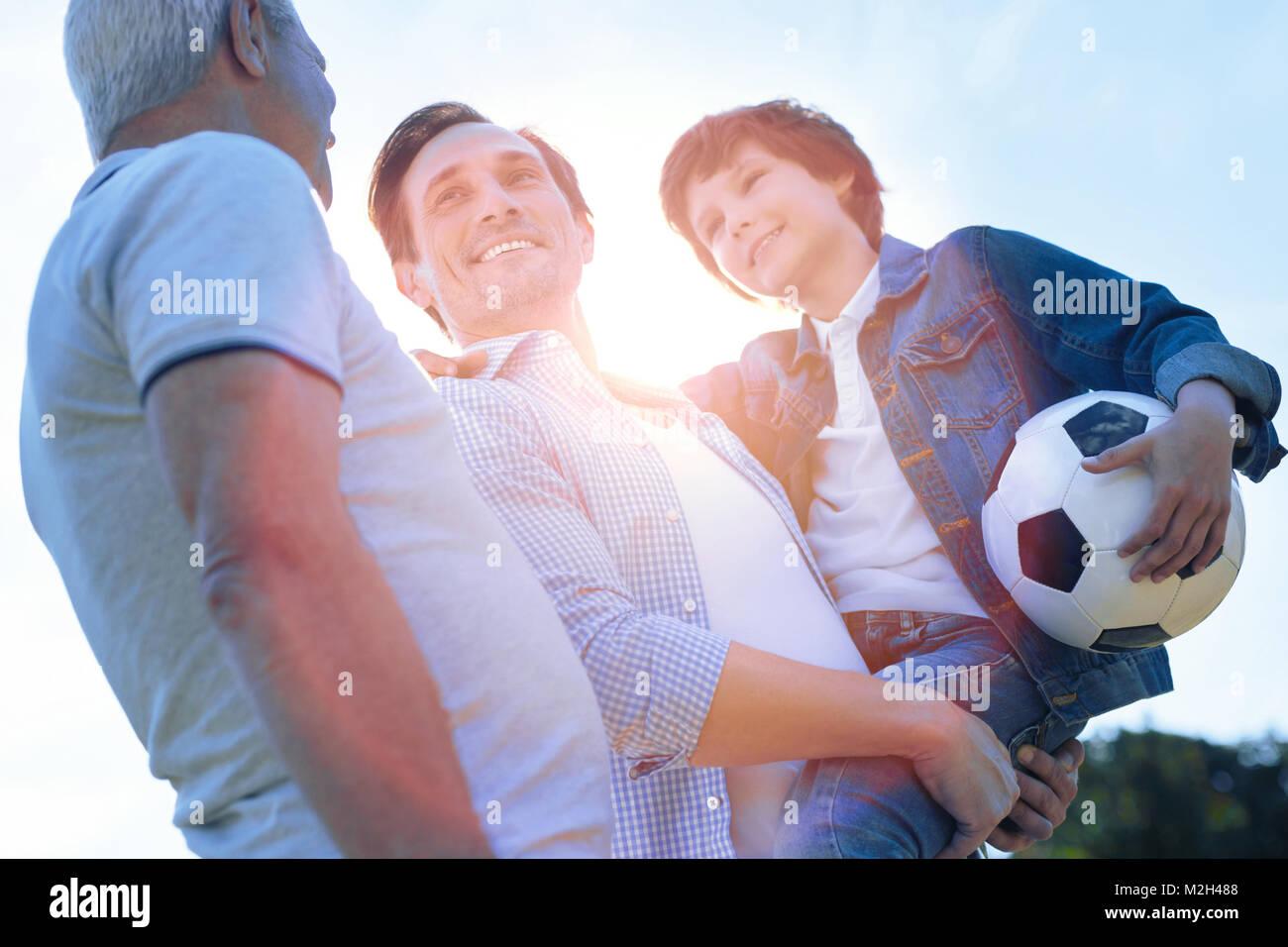 Famiglia allegra discutendo soccer dopo la riproduzione all'aperto Foto Stock