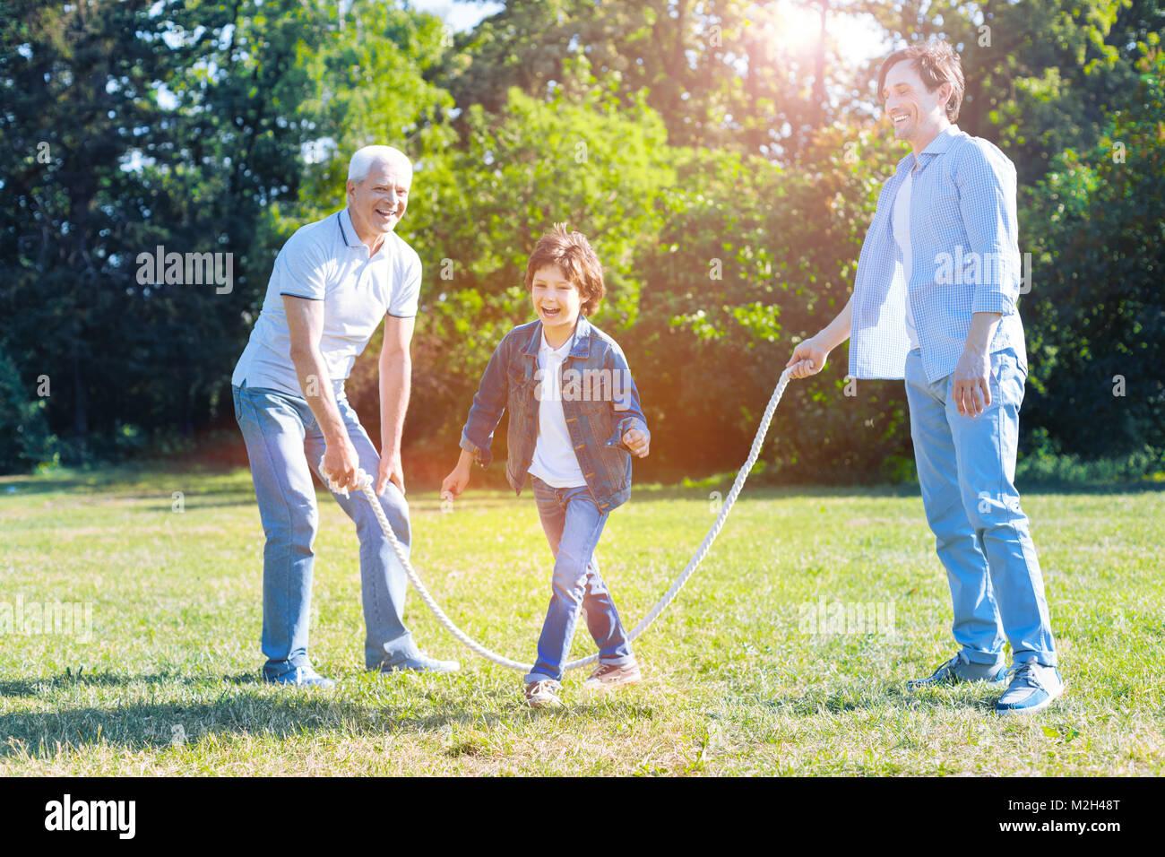 Radiant famiglia multigenerazionale divertendosi con saltare la corda Immagini Stock