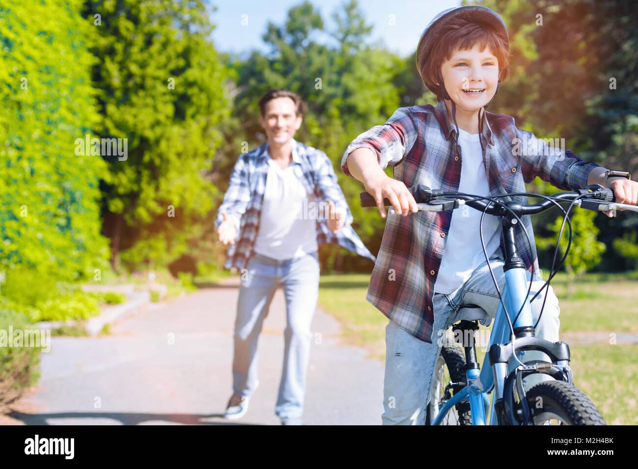 Memori padre figlio di insegnamento caldo a guidare la bicicletta Immagini Stock