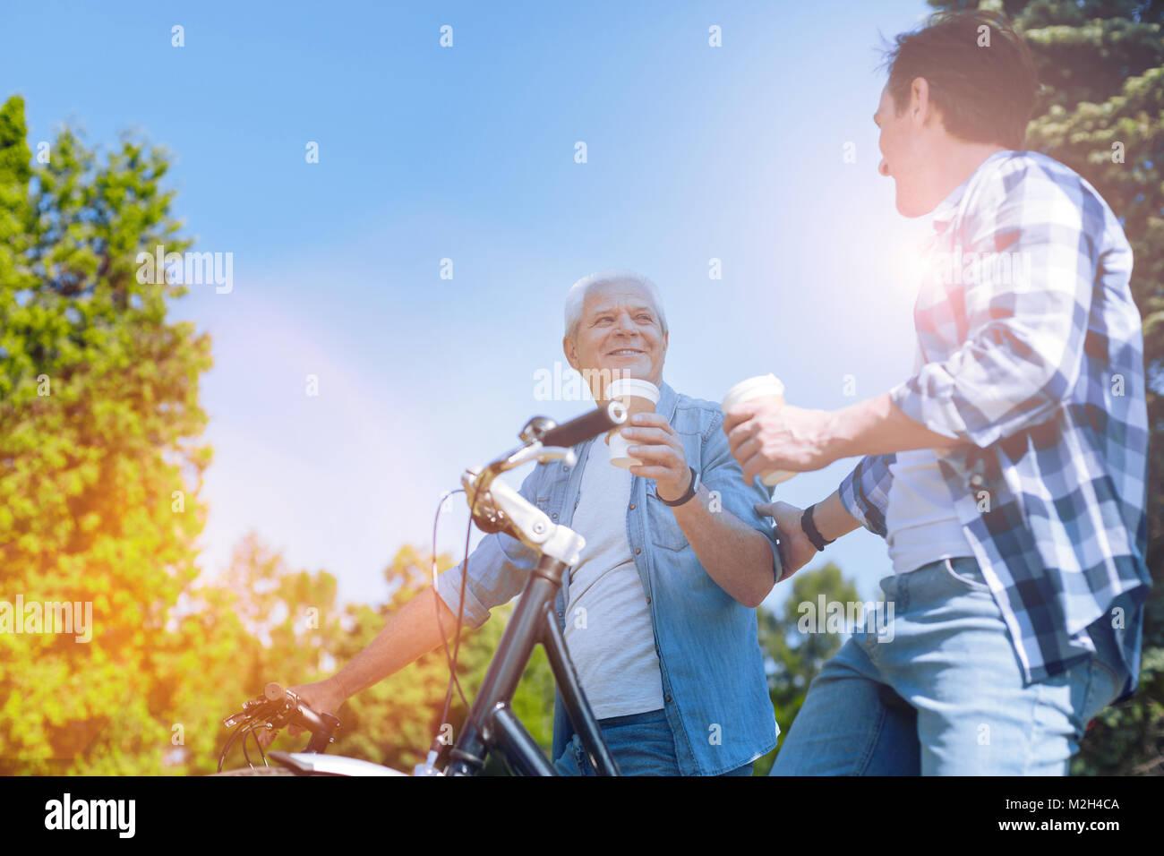 Famiglia armoniosa in chat durante il giro in bicicletta Immagini Stock