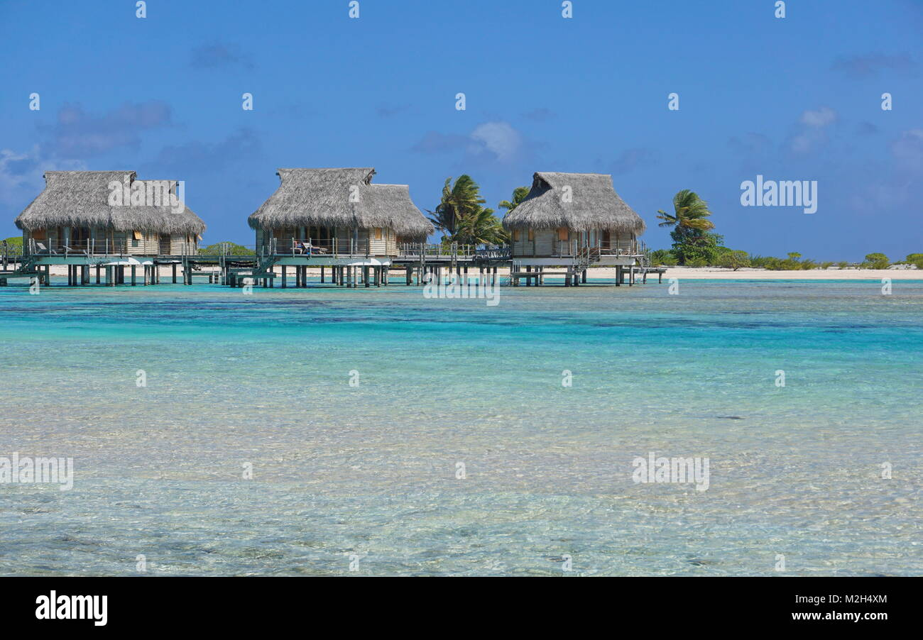 Tropical bungalows sull'acqua nella laguna, Tikehau Atoll, Tuamotus, Polinesia francese, oceano pacifico, Oceania Foto Stock