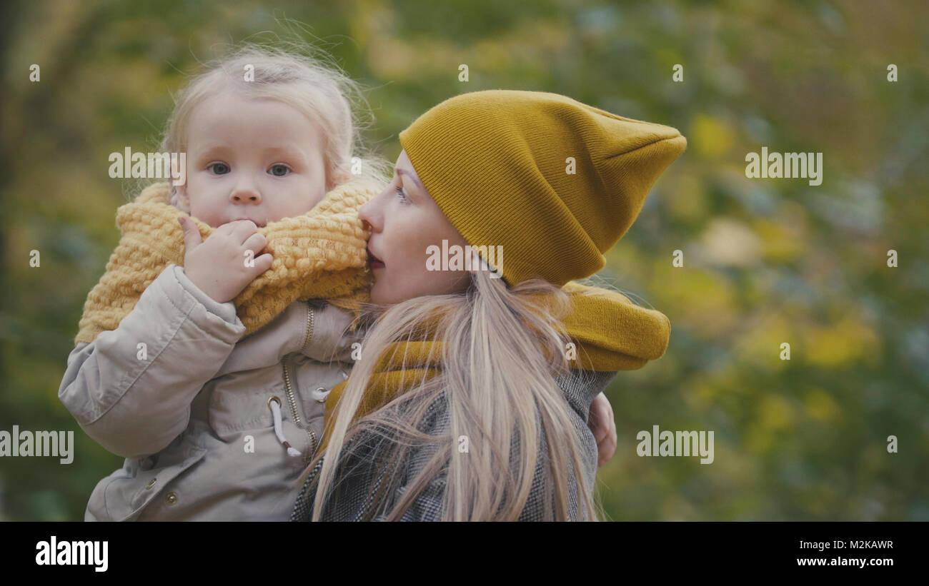 Piuttosto piccola figlia con la sua mamma passeggiate nel parco di autunno Foto Stock
