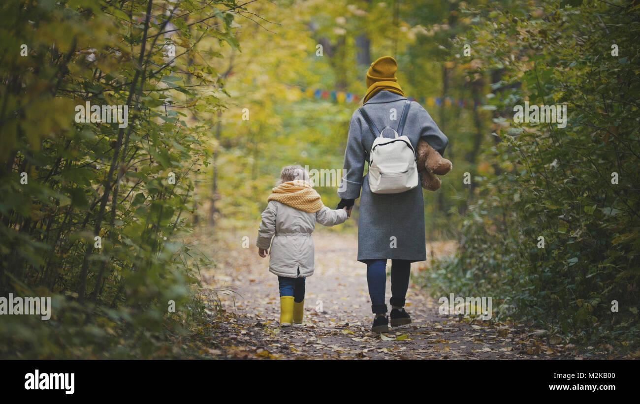 Gioiosa bambina con la sua mamma e Teddy Bear passeggiate nel parco di autunno, vista posteriore Foto Stock
