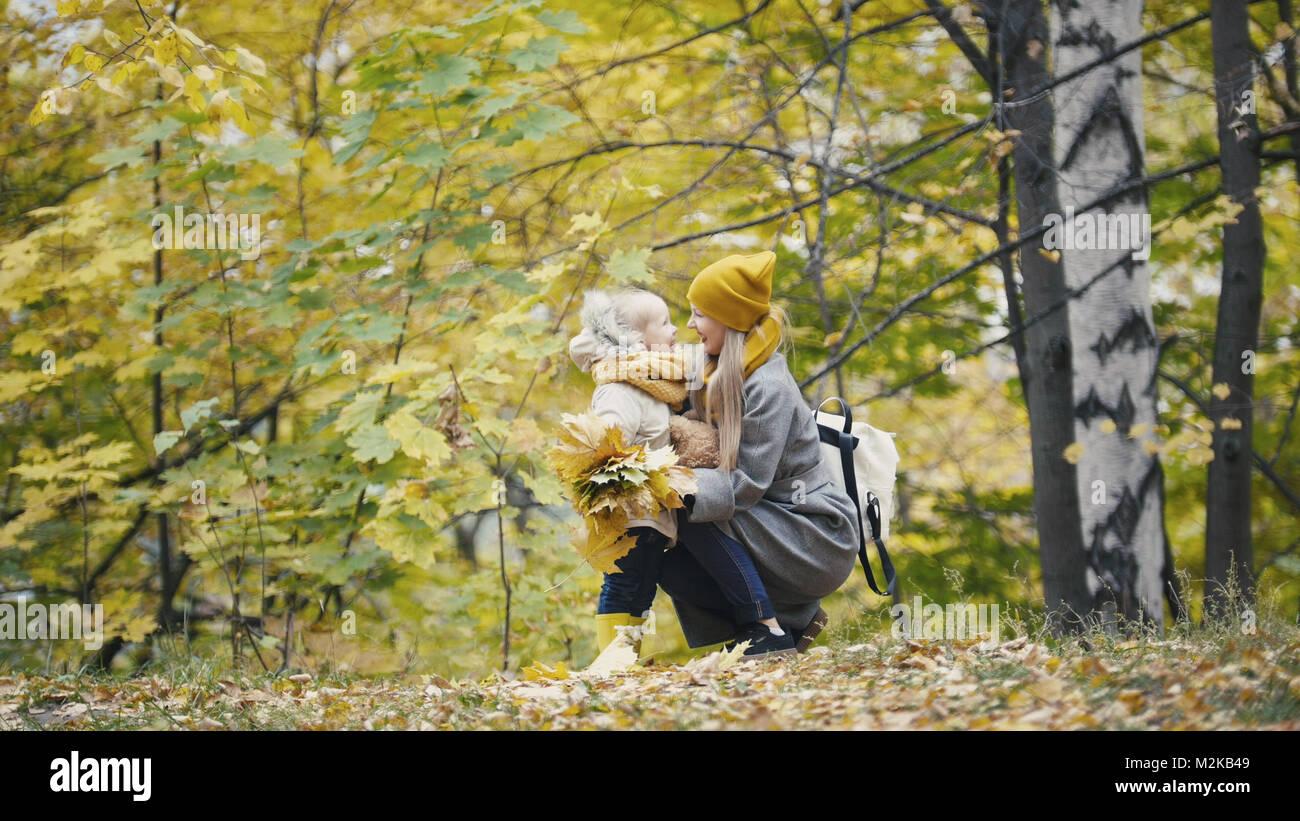 Piuttosto piccola figlia con la sua mamma passeggiate nel parco di autunno - abbraccia Immagini Stock