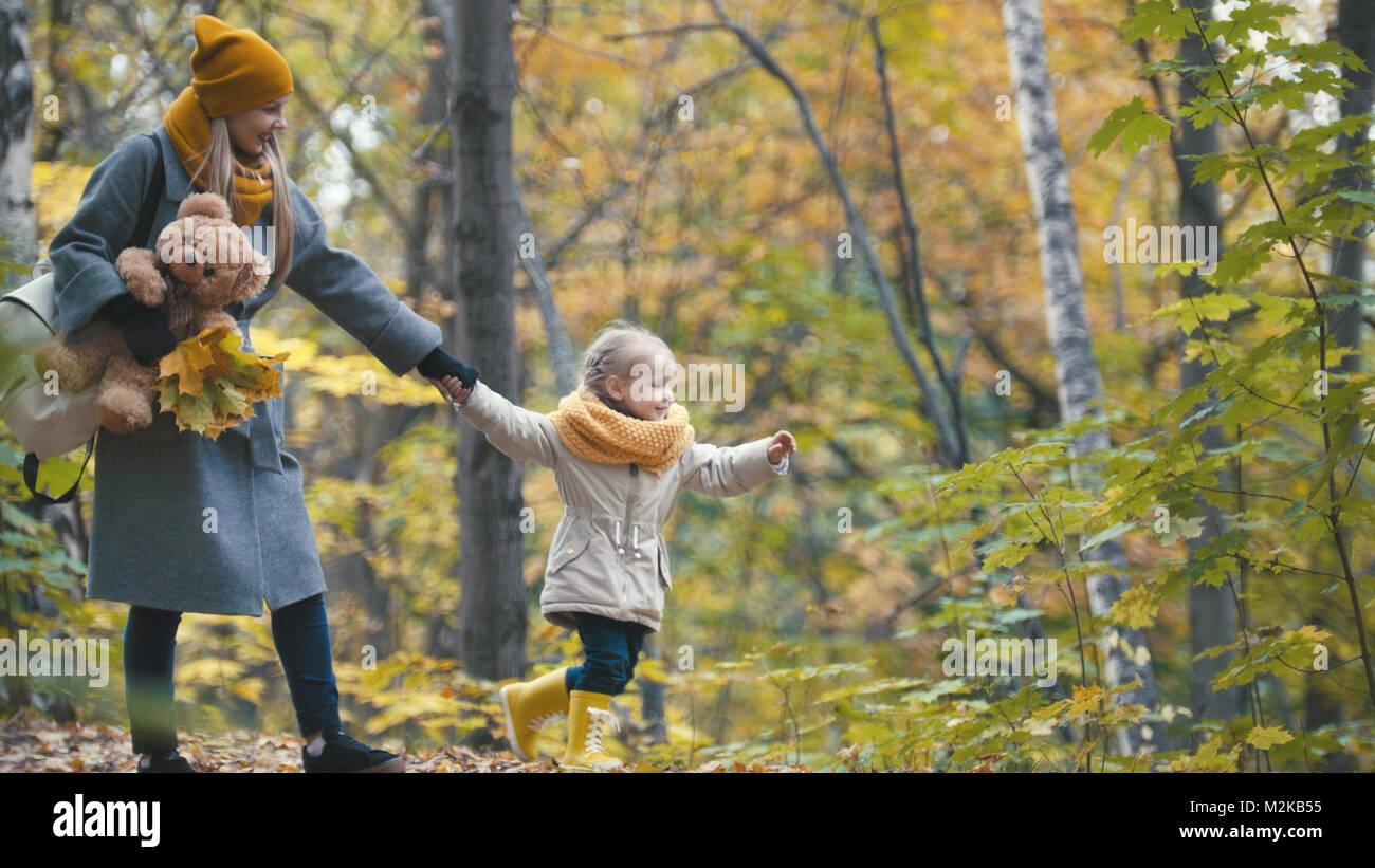 Bella bionda bambina con la sua mamma passeggiate nel parco di autunno - sono divertenti e raccogliere foglie Foto Stock