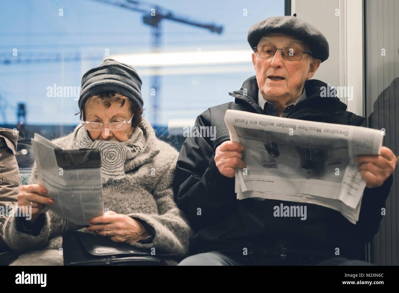 Coppia di anziani leggendo il giornale con la S-Bahn Berlin. Immagini Stock