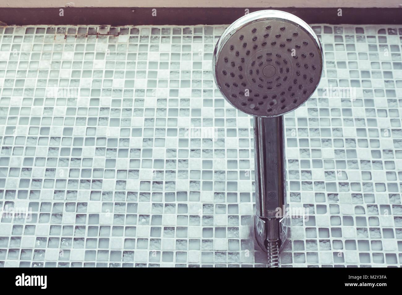 Close up argento vecchio soffione della doccia con verde piastrelle