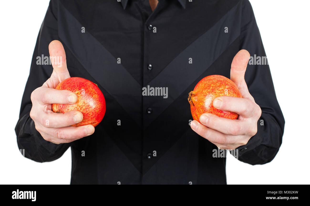 Chiudere l immagine dell uomo in nero che tiene mature melograno, alta frutta antiossidante Immagini Stock
