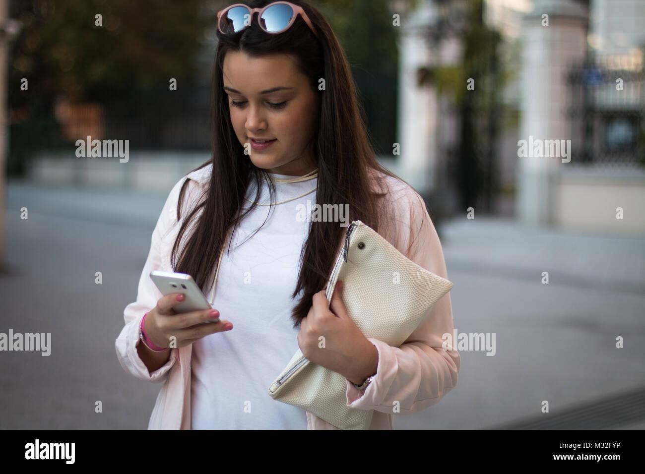 83bbc6b6c1b7 Giovane e bella donna utilizza lo smartphone all esterno. Semplice un  abbigliamento elegante e