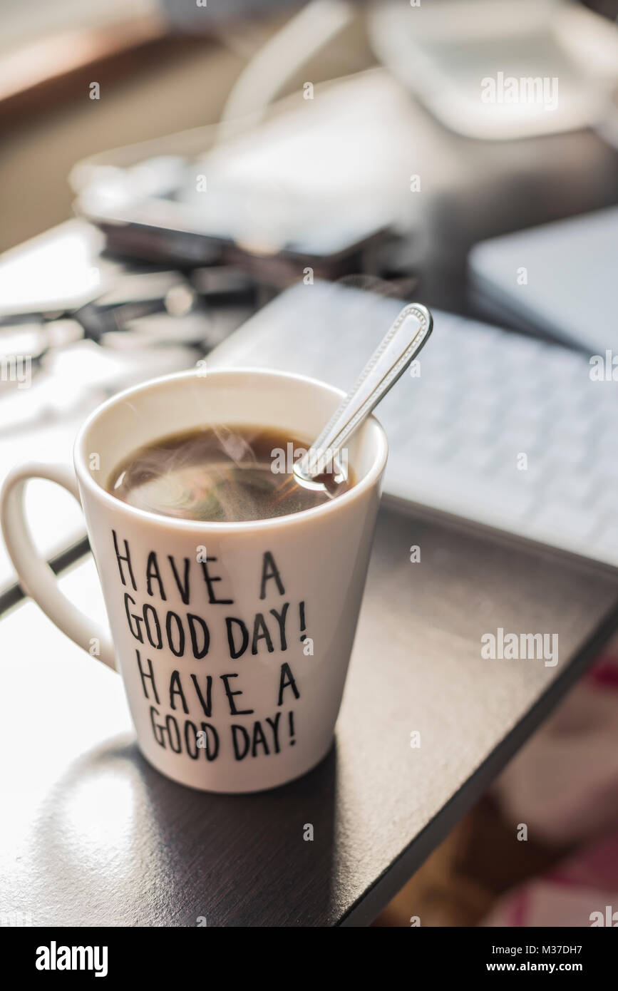 Caffè del mattino in una tazza con il messaggio 'Buon giorno' su uno sfondo blury desktop Immagini Stock