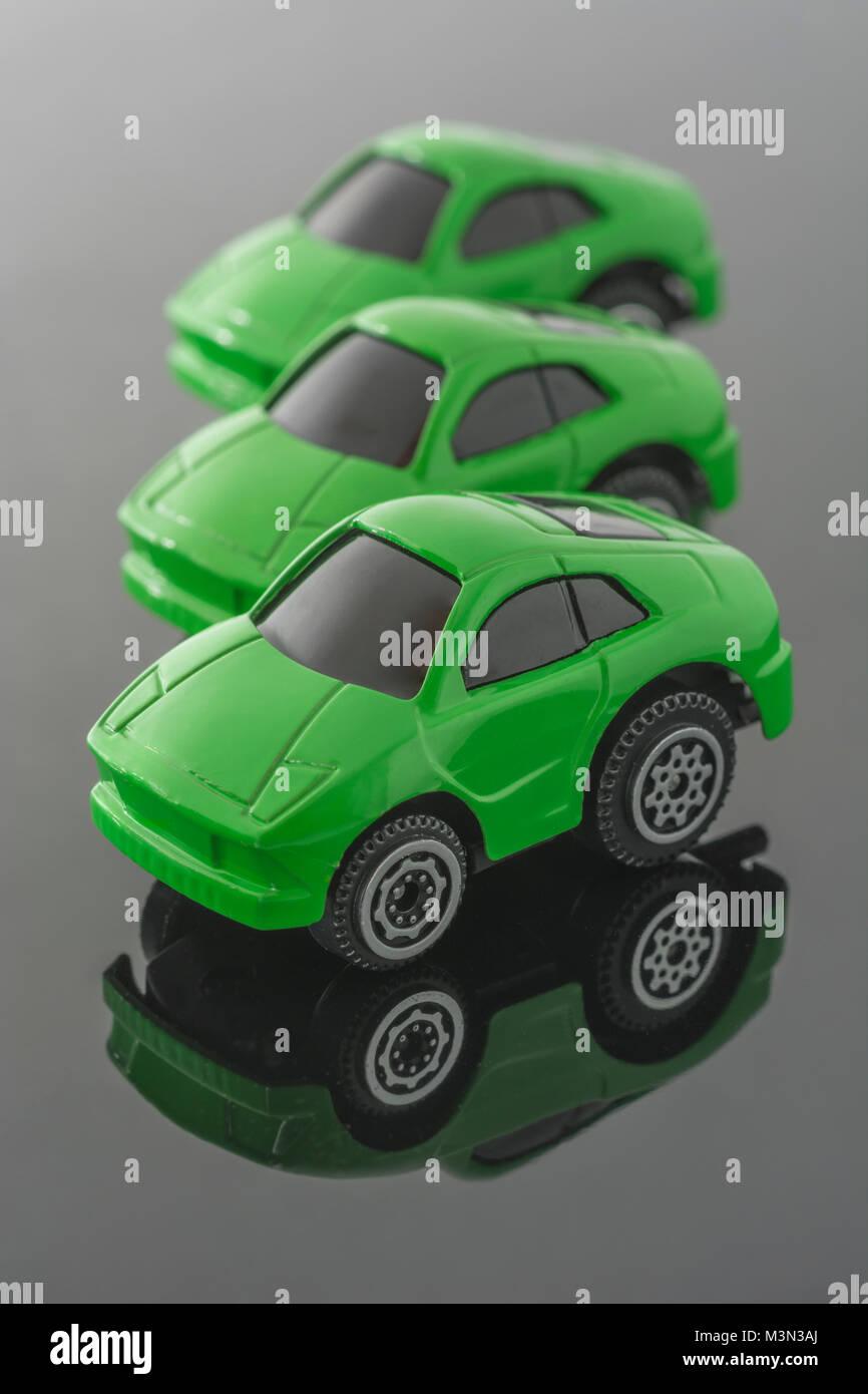 Tre verdi automobili giocattolo su sfondo riflettente. Metafora Green Cars, i veicoli Tesla, carbon footprint, imposta Immagini Stock