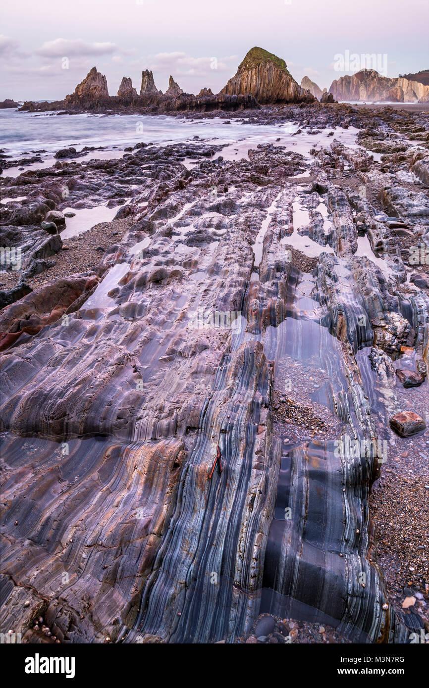 Spiaggia rocciosa durante il tramonto - La Gueirúa, Asturias Immagini Stock