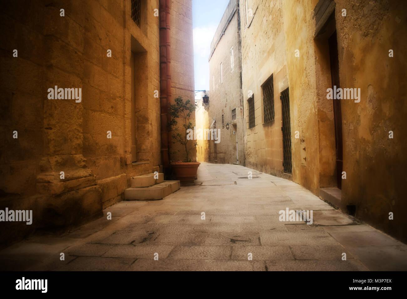 Un tipico stretta e storica strada comprensiva di pareti in ciottoli di Mdina, Malta. Immagini Stock