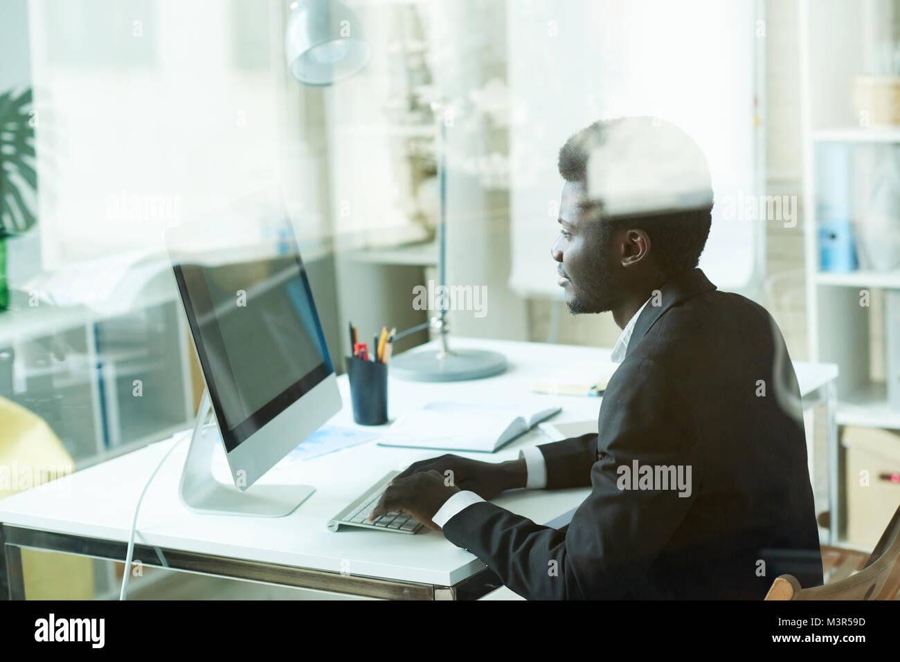 Successo imprenditore africano tramite PC Immagini Stock