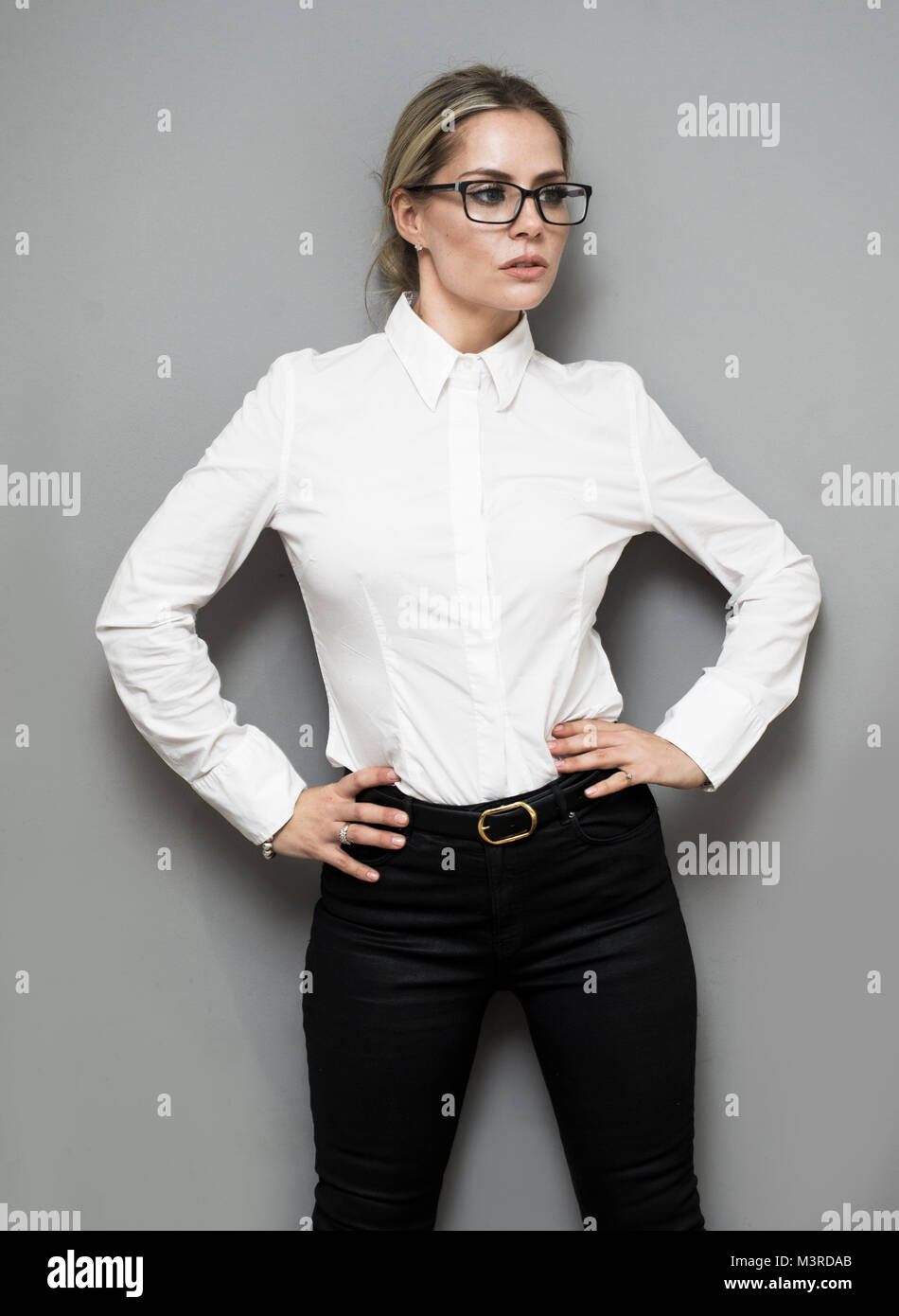 f62835d8c8c255 Attraente giovane donna di affari in camicia bianca con gli occhiali contro  un muro grigio Immagini