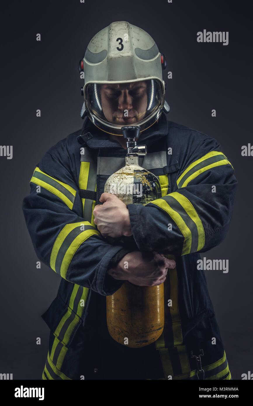 Firefighter rescue giallo detiene il serbatoio di ossigeno. Immagini Stock