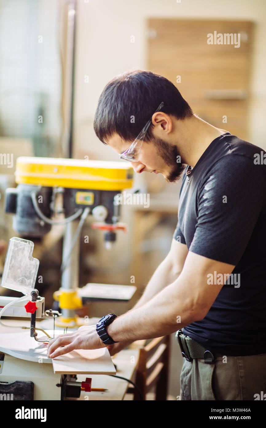 Carpenter impegnate nella lavorazione del legno alla segheria. Immagini Stock