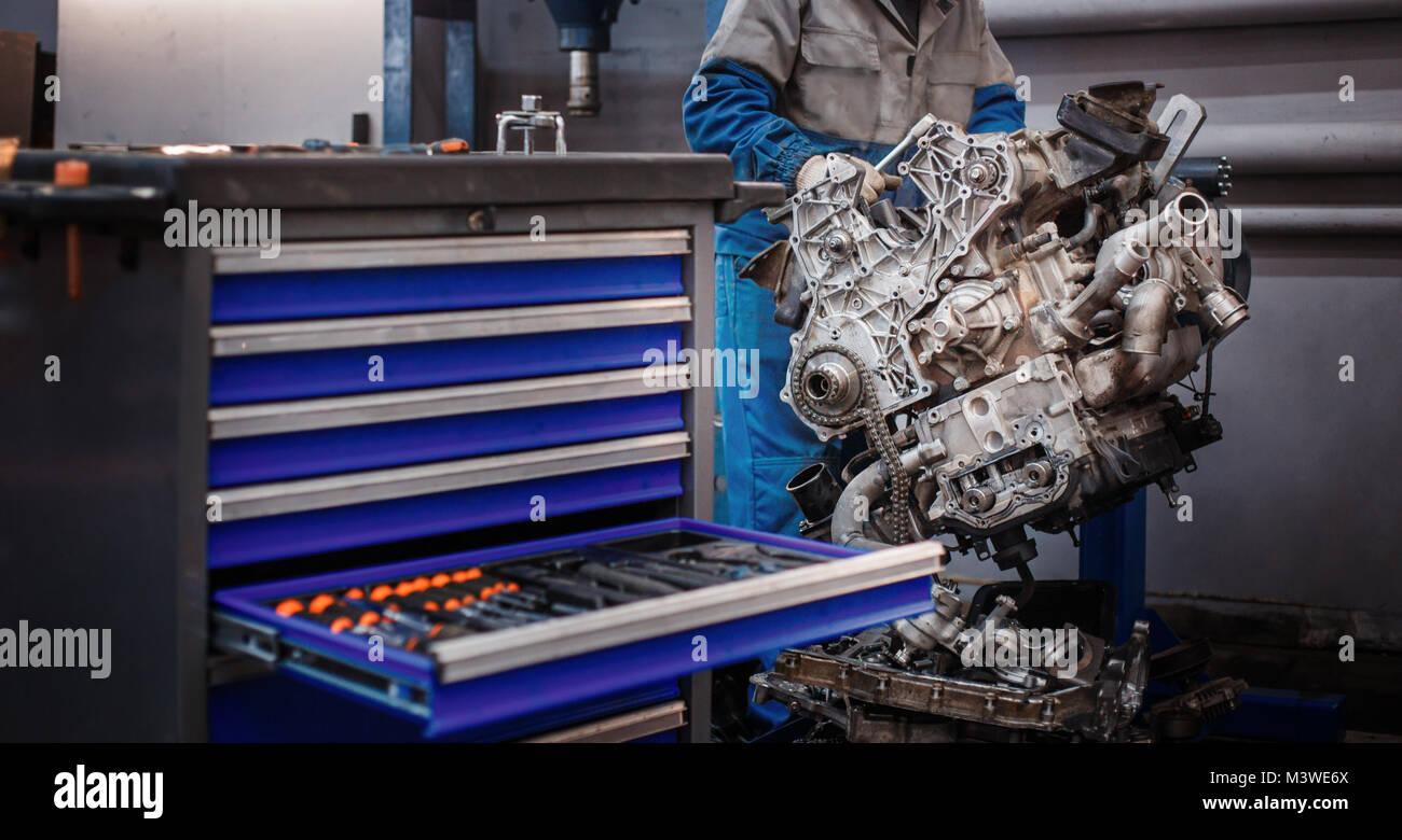 Revisionare la riparazione. Il giovane meccanico automatico smantella il motore di contrasto per la diagnosi e la riparazione presso lo stand in officina. Foto Stock