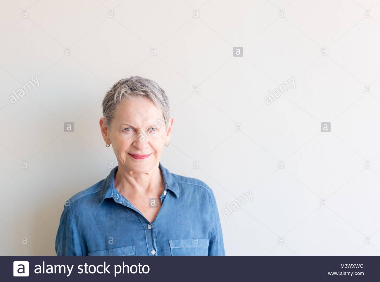 Bella donna anziana con corti capelli grigi e colpire gli occhi blu contro  uno sfondo neutro b7f9d5046960