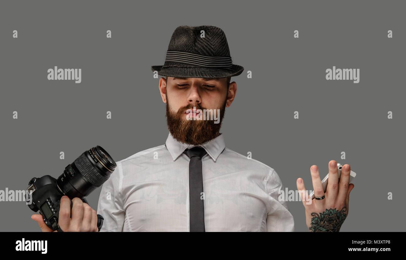 Un uomo con una reflex digitale isolato su sfondo grigio. Immagini Stock