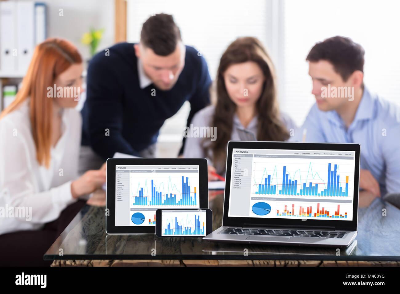 Display grafico su vari moderni dispositivi elettronici schermo oltre la scrivania in ufficio Immagini Stock