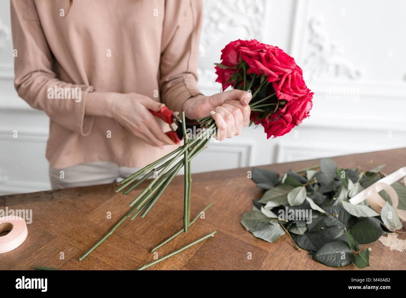 Giovane donna fioraio disponendo le piante nel negozio di fiori. Persone, business vendita fiorai e concetto. Bouquet Immagini Stock