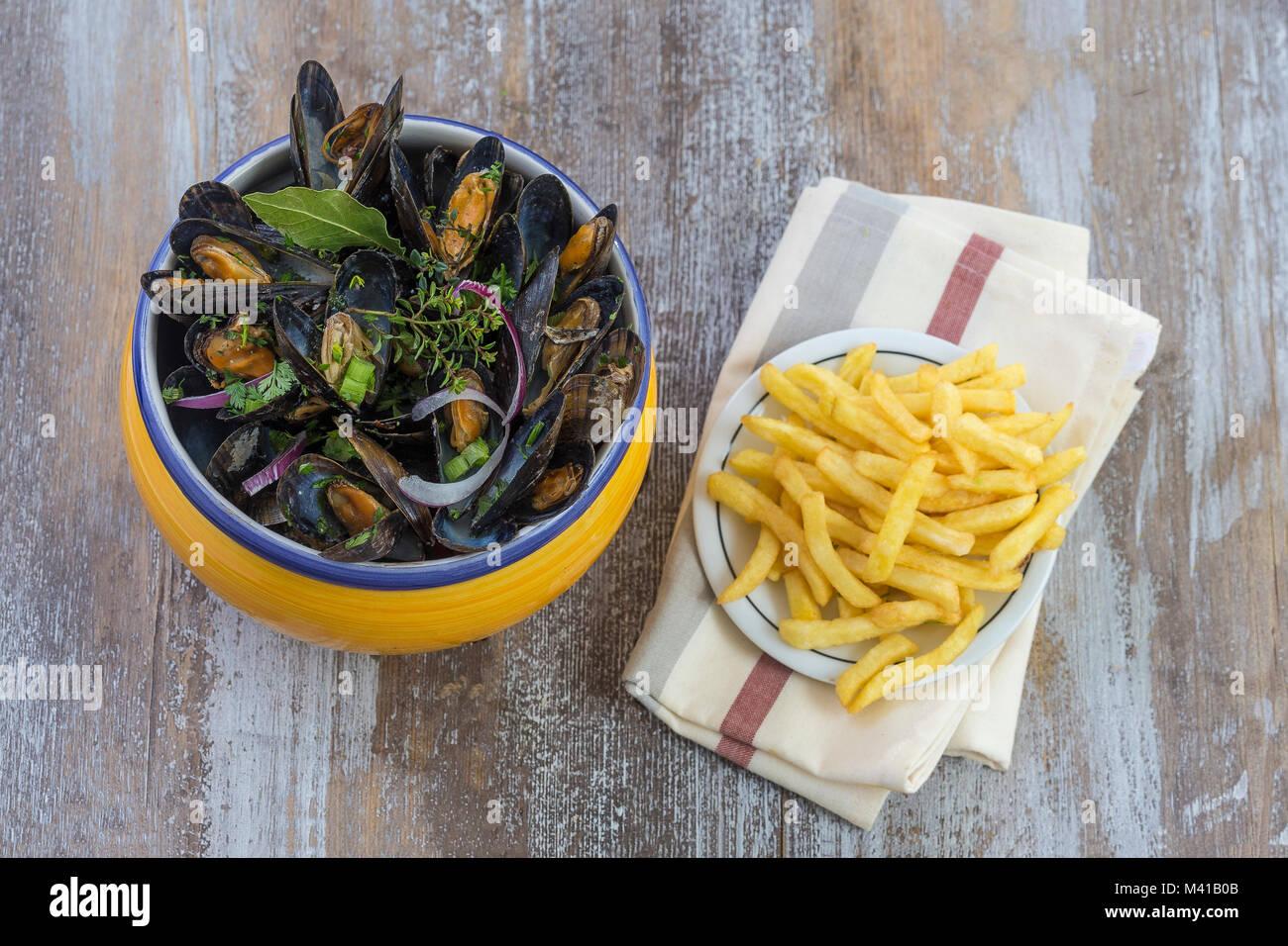Blu francese cozza con le erbe in una vaschetta di colore giallo con patatine fritte di vetro su ramekin tovagliolo Immagini Stock