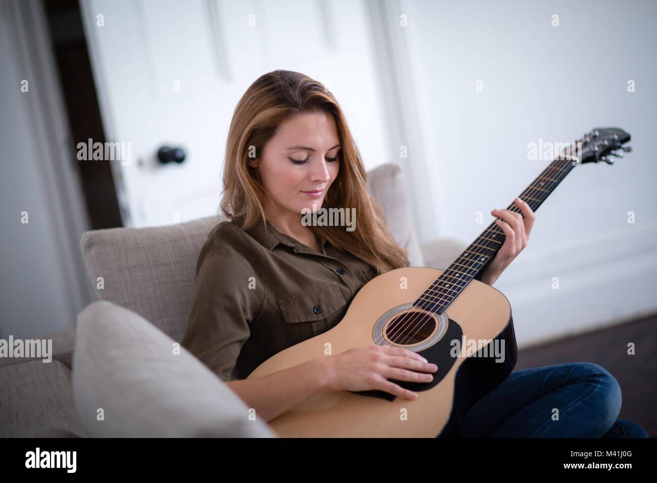 Giovane femmina adulta suonare la chitarra acustica Immagini Stock