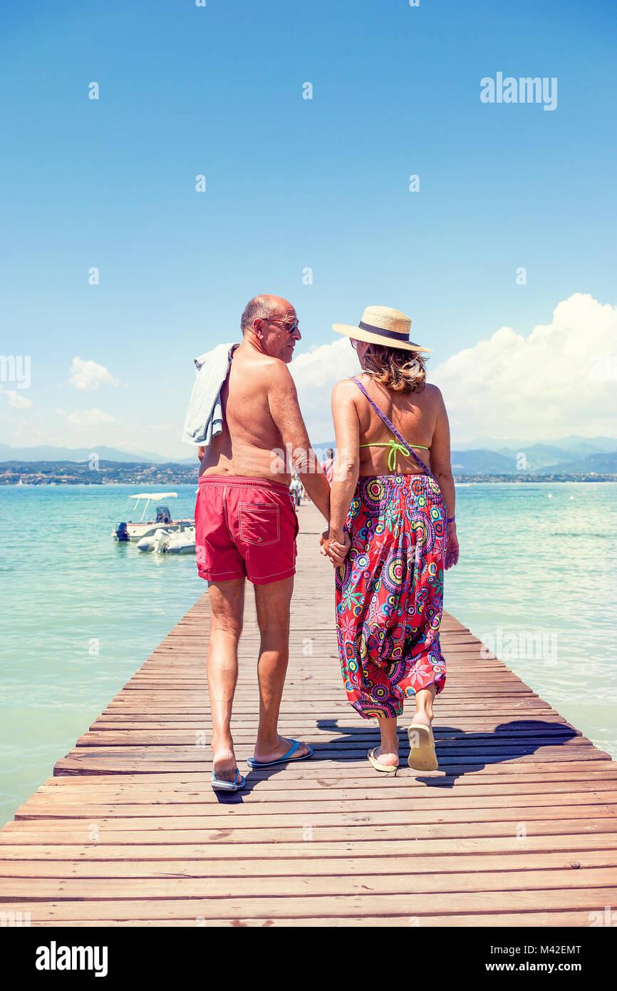 Moderna Coppia matura rilassante in costume da bagno tornare indietro a piedi sul dock di un resort. Concetto di Immagini Stock