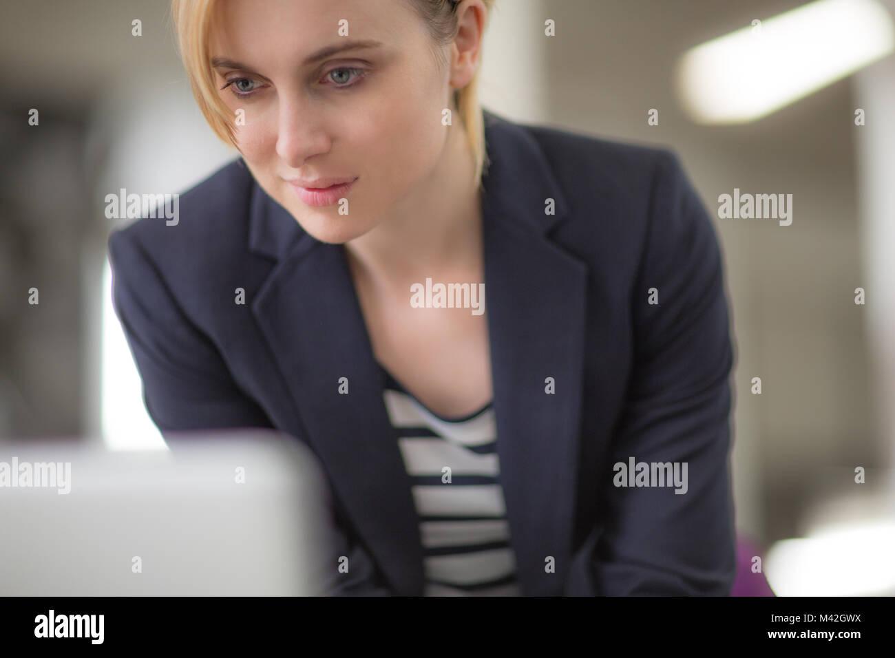 Giovane femmina adulta che guardano un notebook Immagini Stock