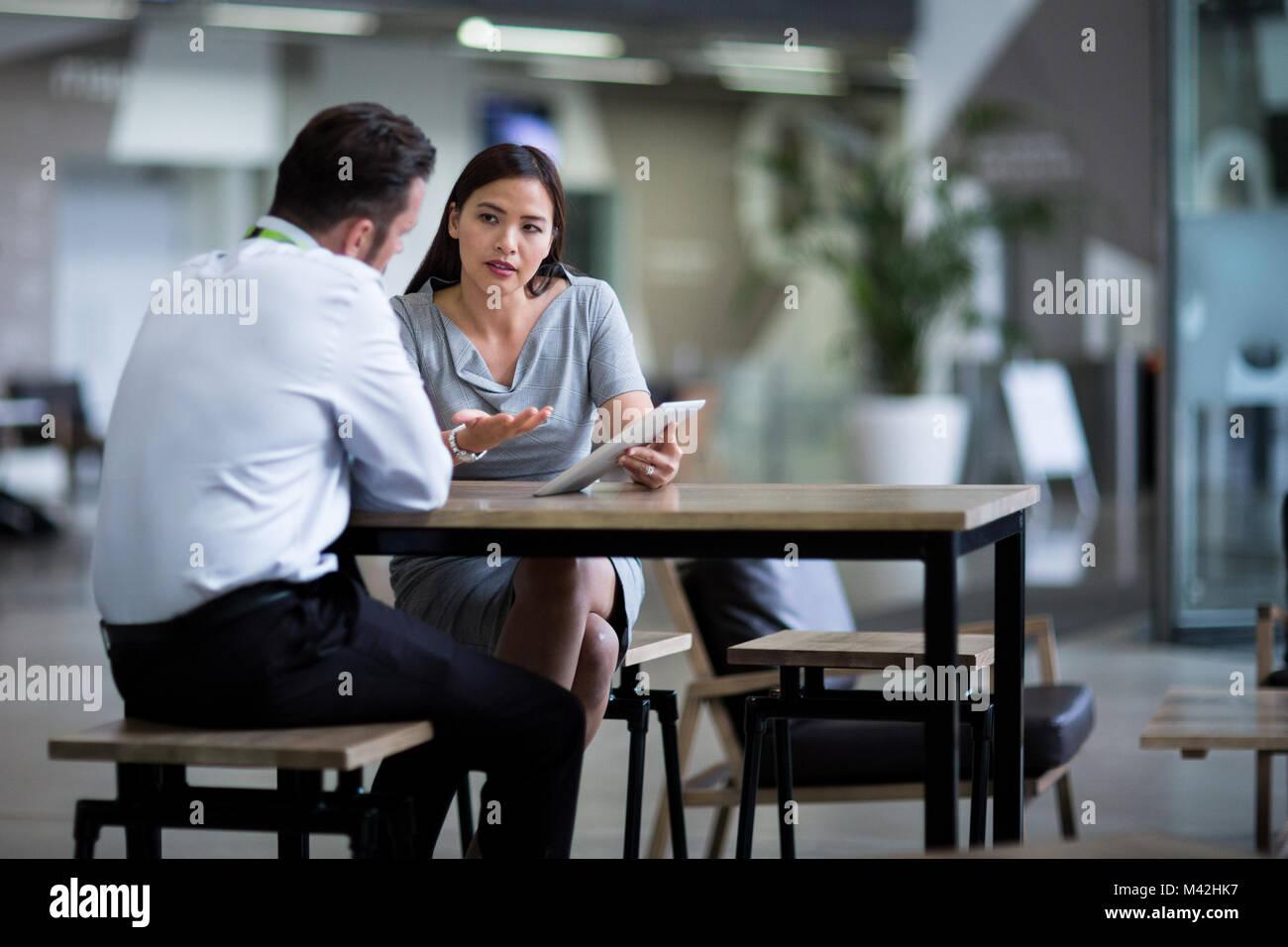 Imprenditrice in una riunione utilizzando una tavoletta digitale Immagini Stock